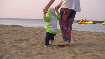 barefooted : Mother helps her little son to make first steps on a beach. Handheld shot Stock Footage