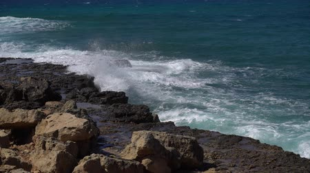 boulders : Wave crashes on long rocky shore and splashes as white foam. Sunny day at the sea Stock Footage