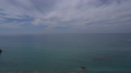 view from below : Panning shot of tuquoise sea and cloudy sky from high cliff Stock Footage