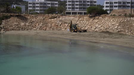earthworks : Tractor works near the water. Improving of sandy beach of sea resort. Panning shot
