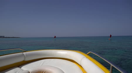 motorbot : Motorboat moves away from beach in blue sea. POV shot from the head of the boat