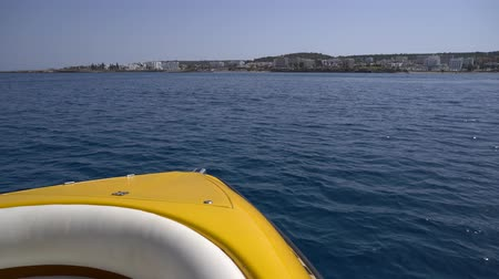 first person : Motorboat moves towards the coast with white hotals and beaches. POV shot from the head of the boat