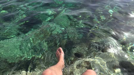 barefooted : Caucasian man sits and splashes his bare feet in azure transparent sea. POV shot