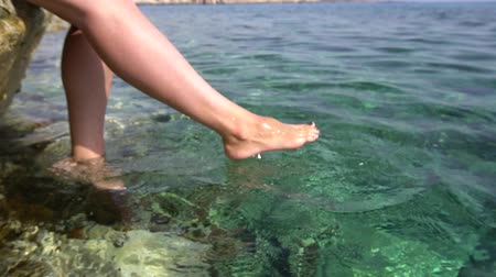 barefooted : Female legs swinging in turquoise sea. Slow motion, unfocused