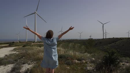 kypr : Girl against the wind farm with open arms in fluttering dress. Handheld shot Dostupné videozáznamy