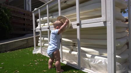 barefooted : Cute toddler boy in a straw hat stands near the white wooden construction. Handheld shot Stock Footage