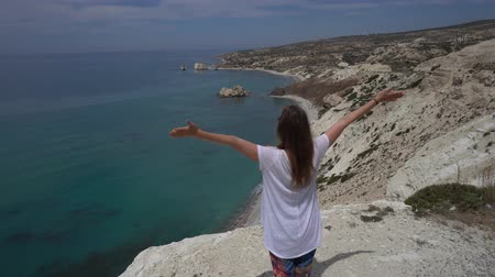 aşağıda : Woman stays on a cliff and opens arms to beautiful sea far below. Point of view changes to top angle