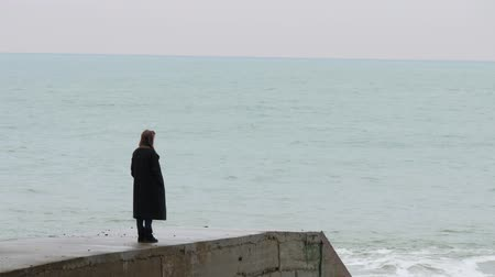 dalgakıran : Lonely woman on concrete breakwater looks at the distance. Cold sea and overcast sky. Handheld shot