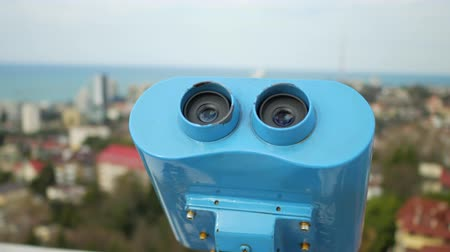 binocular : Tourist binocular telescope for viewing the city near the sea. Handheld shot
