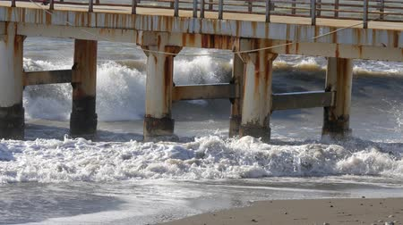 seixo : Foaming waves crashes on rusty metal pier on a sandy sea shore. Handheld shot Stock Footage