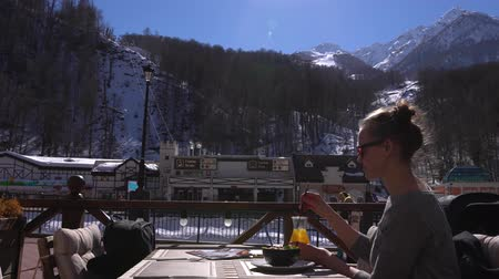 столовая гора : Woman has breakfast on a terrace in alpine ski resort. Rosa Khutor, Krasnaya Polyana, Russia