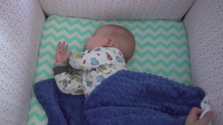 cradle : Adorable baby sleeps in his bed. Female hands cover child with blue blanket. Top view, handheld shot