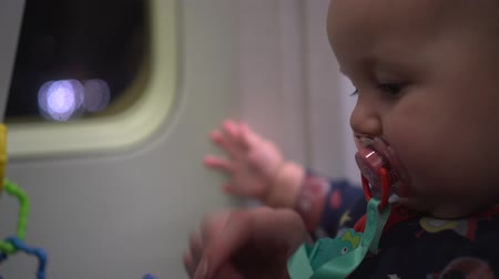 невинный : Close up of cute baby with soother in an airplane moving on runway. Handheld shot