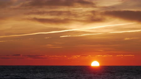 highlights : Timelapse of vivid sunset sky: sun setting into the sea, sky darkening