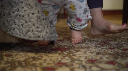 barefooted : Learning to walk. Low angle shot of baby and female adult feet