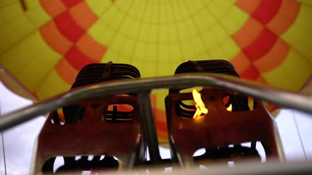 vzducholoď : Fire of hot air balloon burner and bright yellow envelope. Low angle handheld shot
