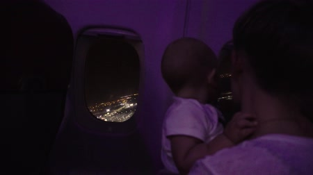 see off : Mother and baby look out of side window. Airpllane takes off over night city
