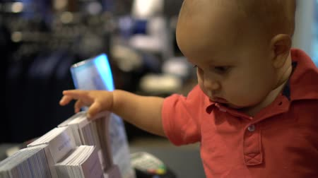 broszura : Baby looks through and touches promotional booklets of glossy paper. Handheld slow motion shot