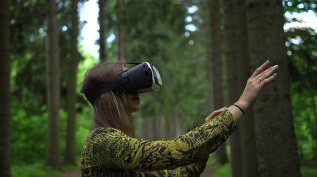 достигать : Woman tries to catch virtual objects playing with VR headsetin a forest Стоковые видеозаписи