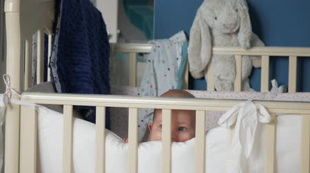 cradle : Toddler stands up in crib, looks out from pillow and happily smiles
