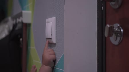 press wall : Baby turns off switch on a wall and lights go out. Close up shot of childs hand