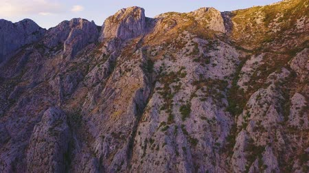 kotorska : Sunlight and shadows on rocky slopes of a mountain at sunset. Panning shot Stock Footage