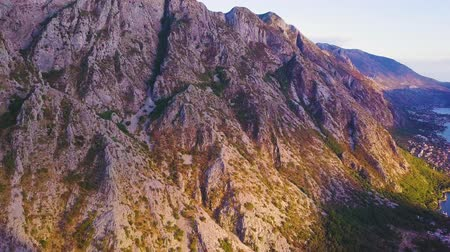 stony : Sunset light and shadows on a mountain at the shore of Kotor Bay. Aerial shot Stock Footage