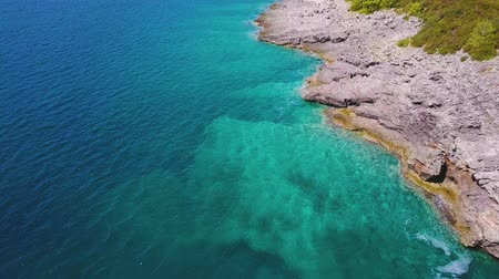 denteado : Aerial of rocky coastline and turquoise sea. Sea bottom is visible through transparent water