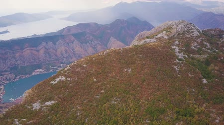 telha : Flying over ridge with a view on coastal town between mountains. Aerial of Bay of Kotor, Montenegro