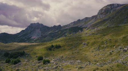 balkan : Rocky peaks and highlands of Montenegro mountains. Sun shines through clouds. Panning shot Stock Footage
