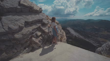 into the camera : Woman tourist stay on a cliff edge and looks into the distance. Lovchen, Montenegro Stock Footage