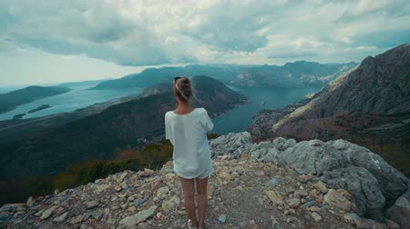 příkrý : Woman on a stony mountain summit looks at sea Bay of Kotor. Lovchen, Montenegro Dostupné videozáznamy