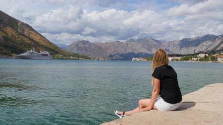 kotorska : Woman sits on a pier and looks on beautiful Bay of Kotor among mountains Stock Footage
