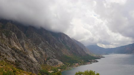 адриатический : Stormy clouds on the top of rocky mountain ridge at the shore of sea bay in Montenegro