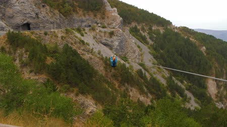 zip line : Zip-line in mountains. Man helps a woman to lounch pushing her for higher speed