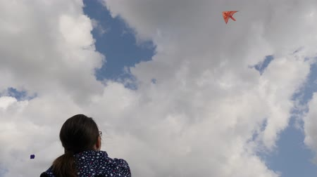 transportado pelo ar : Low angle view of a girl handling a bright orange kite with a bird flying high above