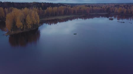fly fishing : Small motor boat floats on rippling blue water of the lake among autumn forest. Aerial shot