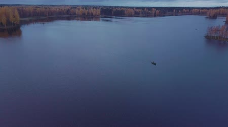 birch : Flying over blue lake among fall forest. Lonley small boat floats on rippling waters