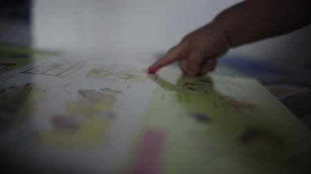 pontos : Baby points with his finger at drawings in illustrated book. Shallow depth of field