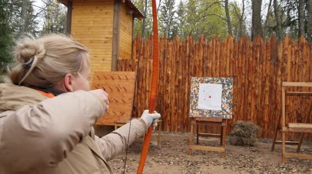 tiro com arco : Blond woman shoots with red longbow and hits the target with arrow