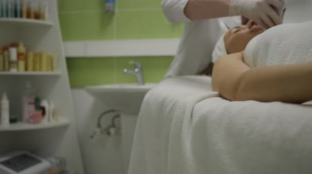 расслаиваться : Relaxed woman gets ultrasound facial cleansing treatment in cosmetology salon