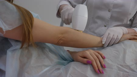 sensível : Hands of woman getting cosmetology lase treatment in beauty salon. Close up