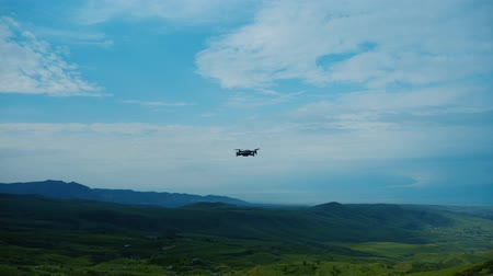 armenia : Drone flies away into the cloudy sky above green mountains