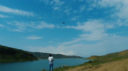 propeller toy : Young man on a lake shore controls drone flying in blue sky with white clouds Stock Footage