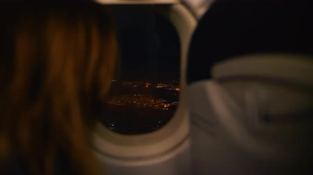 megalopolis : Woman looks at night city lights from side window of flying airplane Stock Footage