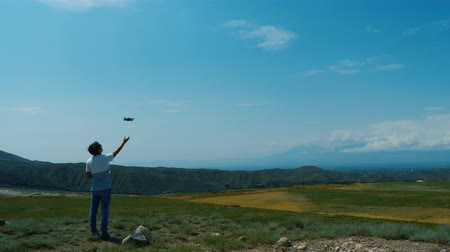 zumbido : Young man lands little drone on his hand against blue sky in Ararat province