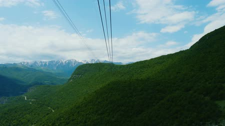 orta hava : Moving on cableway above green forest on slope in Caucasus mountains Stok Video