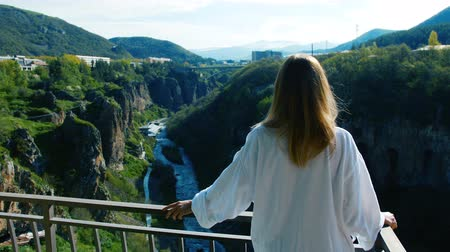 íngreme : Woman stands at balcony and looks on river flowing in deep narrow gorge
