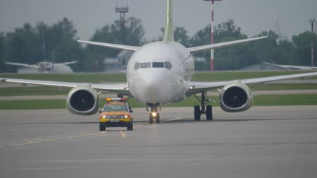 el feneri : MOSCOW, RUSSIA - JULY 25, 2018: Boeing 737 moves behind follow me car on taxiway in Sheremetyevo airport Stok Video
