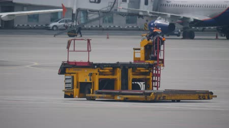 aerodrome : MOSCOW, RUSSIA - JULY 25, 2018: Ground support equipment in Sheremetyevo Airport. Orange baggage loadre moves towards an aircraft
